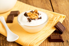 Yogurt with Chocolate and Nuts. Plain Organic Yogurt with Some Chocolate, Mint and Nuts in Bowl. Homemade dessert on rustic wooden table close up royalty free stock image