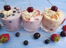 yogurt, ciliegia deliziosa dell'albicocca del rinfresco della fragola del mirtillo della farina d'avena su un fondo di legno blu immagini stock