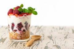Yogurt con i muesli e le bacche in vetro sulla tavola di legno leggera fotografie stock