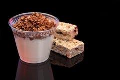 Yogurt con il granola del chocolade e la barra di granola con i frutti ed i dadi Fotografia Stock Libera da Diritti