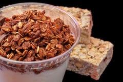 Yogurt con il granola del chocolade e la barra di granola con i frutti ed i dadi Immagine Stock Libera da Diritti
