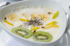 Yogurt con il kiwi di chia del mango in piatto ceramico bianco con le tovaglie bianche fotografie stock libere da diritti