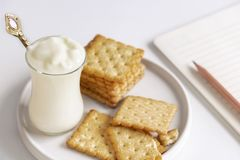 Yogurt and cookies is a healthy breakfast. Yogurt made from milk fermented by added bacteria, often sweetened and flavored.  royalty free stock image
