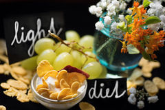 Yogurt, corn flakes, wine grape, flowers and handwritten inscription Royalty Free Stock Photos