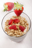 Yogurt with crunchy cereal and strawberry. Creamy yogurt with honey toasted oat and fresh organic strawberry in a glass royalty free stock photo
