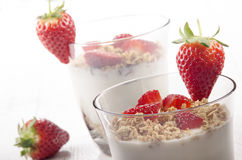 Yogurt with crunchy cereal and strawberry. Creamy yogurt with honey toasted oat and fresh organic strawberry in a glass stock image