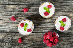 Yogurt in cups with  raspberry, whole grain cereals and corn fla. Homemade yogurt in cups with whole grain cereals and corn flakes and  raspberry, decorated with Royalty Free Stock Images