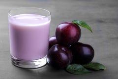 Yogurt dalla prugna e dalle prugne mature fresche con le foglie su un fondo grigio immagine stock libera da diritti