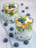 Yogurt dessert with blueberry, kiwi and cereals. In the glass on the cloth Stock Photos
