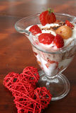 Yogurt dessert with hearts. Refreshing yogurt dessert with strawberries and yellow raspberries and little wicker hearts. Shallow DOF Royalty Free Stock Photo
