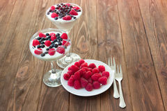 Yogurt dessert with raspberries and blueberries. In glasses on the wooden table Royalty Free Stock Image