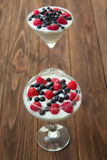 Yogurt dessert with raspberries and blueberries. In glasses on the wooden table Royalty Free Stock Images