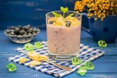 Yogurt di mirtillo, cereale e un ramoscello della menta Fondo blu di legno Vista superiore Primo piano Immagine Stock Libera da Diritti