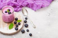 Yogurt di mirtillo cremoso del hommemade fresco con i mirtilli freschi sul bordo di legno d'annata ed il cucchiaio d'argento sull fotografie stock libere da diritti
