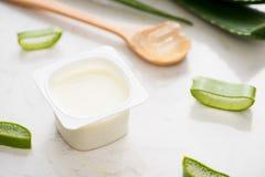 Yogurt di vera dell'aloe con le foglie fresche su una tavola di legno Immagini Stock Libere da Diritti