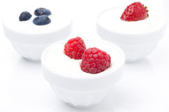 Yogurt with different fresh berries in bowls on white Stock Photos