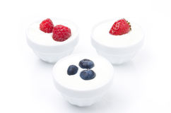 Yogurt with different fresh berries in bowls on white. Yogurt with different berries in bowls on white (with strawberries, blueberries, raspberries Royalty Free Stock Photos