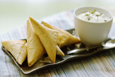 Yogurt and Feta Filo Triangles. A close up image of crunchy butter glazed filo triangles with a cup of yogurt with fresh herbs Royalty Free Stock Images