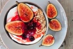 Yogurt with figs, berries and granola, overhead on rustic background. Greek yogurt with sweet figs, berries and granola, overhead scene on rustic background Stock Photography