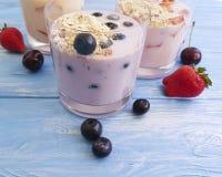 Yogurt, fragola del mirtillo della farina d'avena deliziosa su un fondo di legno blu immagine stock libera da diritti