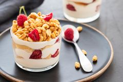 Yogurt fresco con rasberry in vetro trasparente Lamponi in ciotola bianca Prima colazione sana di mattina immagini stock