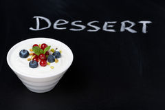 Yogurt with fresh berries on a black background Stock Image