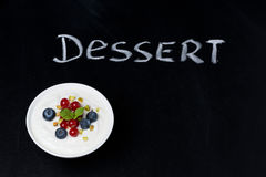 Yogurt with fresh berries on a black background and word dessert Royalty Free Stock Photos