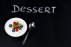 Yogurt with fresh berries on black board and the word dessert Stock Images