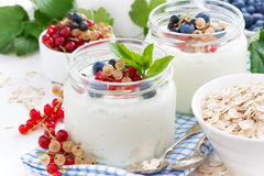 Yogurt with fresh berries and breakfast foods on table Stock Photos