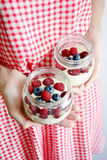 Yogurt with fresh berries. Yogurt with fresh raspberry and blueberry in jar in girl hands. Vertical Royalty Free Stock Images