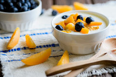 Yogurt with fresh blueberries, corn flakes and apricots. On a textural brown surface Stock Photos