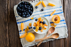 Yogurt with fresh blueberries, corn flakes and apricots, top view Royalty Free Stock Image