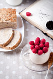 Yogurt with fresh raspberries, bread, tea. Yogurt with fresh raspberries in a glass cup, brown grain bread, book and tea Stock Photo