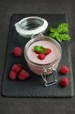 Yogurt with fresh raspberries. In a glass jar on a black slate background Stock Photo