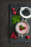 Yogurt with fresh raspberries. In a glass jar on a black slate background Royalty Free Stock Photography