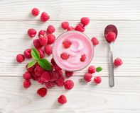 Yogurt with fresh raspberry. On white wooden table. Fresh yogurt. Healthy food concept. High resolution product. Top view Royalty Free Stock Image
