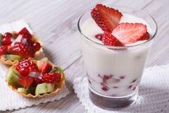 Yogurt with fresh strawberries and fruit tartlets Stock Photo