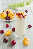 Yogurt with fruit. Yogurt in a glass, apricots and ripe cherries on a wooden background.health and diet concept Stock Photos