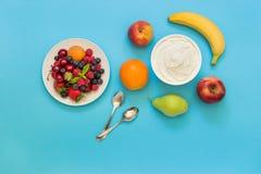 Yogurt and fruits, berries as an ingredients. Greek yogurt around orange, banana, pear, peach, apple, plate with strawberries, raspberries, blueberries and two Stock Image