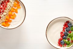 Yogurt with fruits in dishes. On wooden table stock images