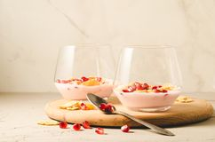 yogurt with garnet grains and flakes in glass/yogurt with garnet grains and flakes in glass on a wooden tray and white background royalty free stock photo