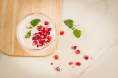 Yogurt. Yogurt with garnet and mint in glass on a wooden tray and the scattered pomegranate seeds on a white table. Top view. stock photography