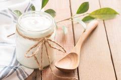 Yogurt in glass bottles on wooden table. Yogurt in glass bottles and wooden spoon on wood table royalty free stock photo