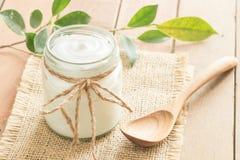 Yogurt in glass bottles on wooden table. Yogurt in glass bottles and wooden spoon on wooden table ad stock image