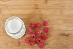 Yogurt in glass jar and raspberries on a wooden background. Yogurt in glass jar and raspberries on a wooden background Stock Photo