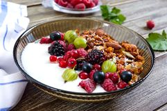 Yogurt, granola, fresh berries in a bowl on a wooden table. Delicious and healthy breakfast. Proper nutrition. Dietary menu.  royalty free stock photography