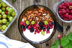 Yogurt, granola, fresh berries in a bowl on a wooden table. Delicious and healthy breakfast. Proper nutrition. Dietary menu. The. Top view, flat lay royalty free stock image