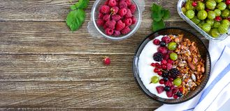 Yogurt, granola, fresh berries in a bowl on a wooden table. Delicious and healthy breakfast. Proper nutrition. Dietary menu. The. Top view, flat lay stock photos