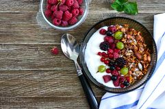 Yogurt, granola, fresh berries in a bowl on a wooden table. Delicious and healthy breakfast. Proper nutrition. Dietary menu. The. Top view, flat lay stock images