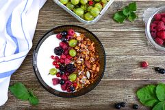 Yogurt, granola, fresh berries in a bowl on a wooden table. Delicious and healthy breakfast. Proper nutrition. Dietary menu. The. Top view, flat lay royalty free stock photos